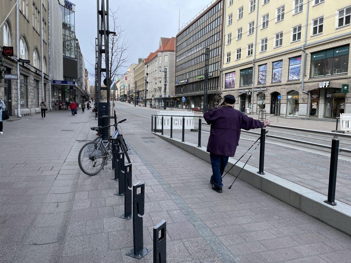 Ihminen nojaa kaiteeseen ja seisoo keskellä pyörätietä Tampereen Hämeenkadulla.