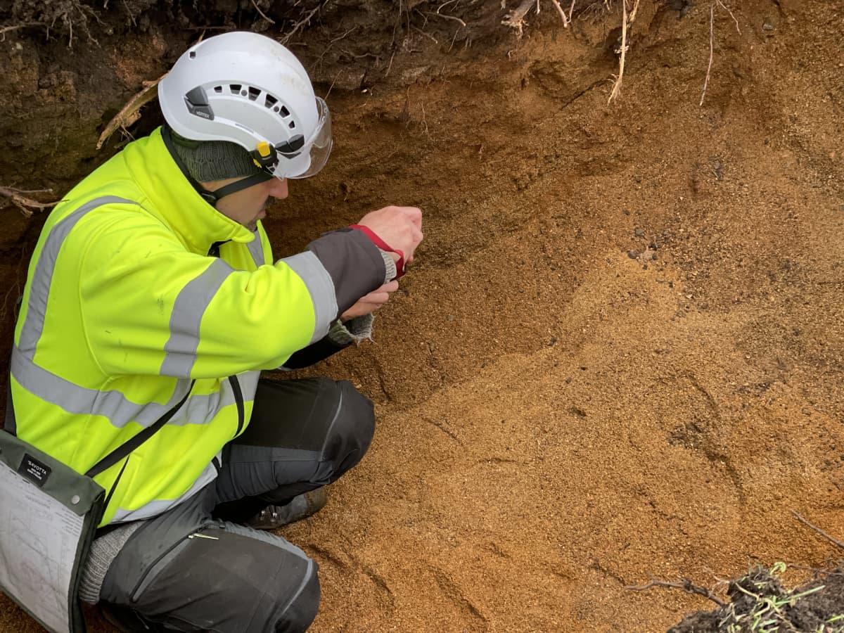 Ville Laakso kaivetun kuopan pohjalla. Maa on ruskeaa hiekkaa.