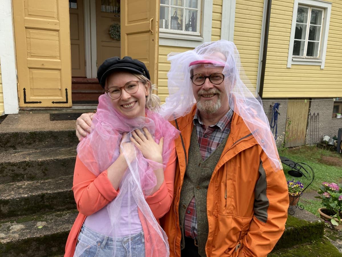 Tytär ja isä seisovat keltaisen puutalon rappujen edessä ja hymyilevät.