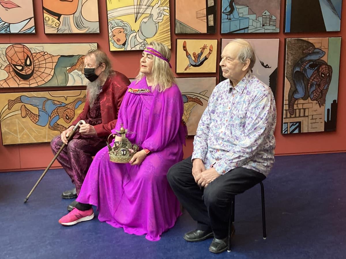 kolme kuvataiteilijaa istuu näyttelyhuoneessa