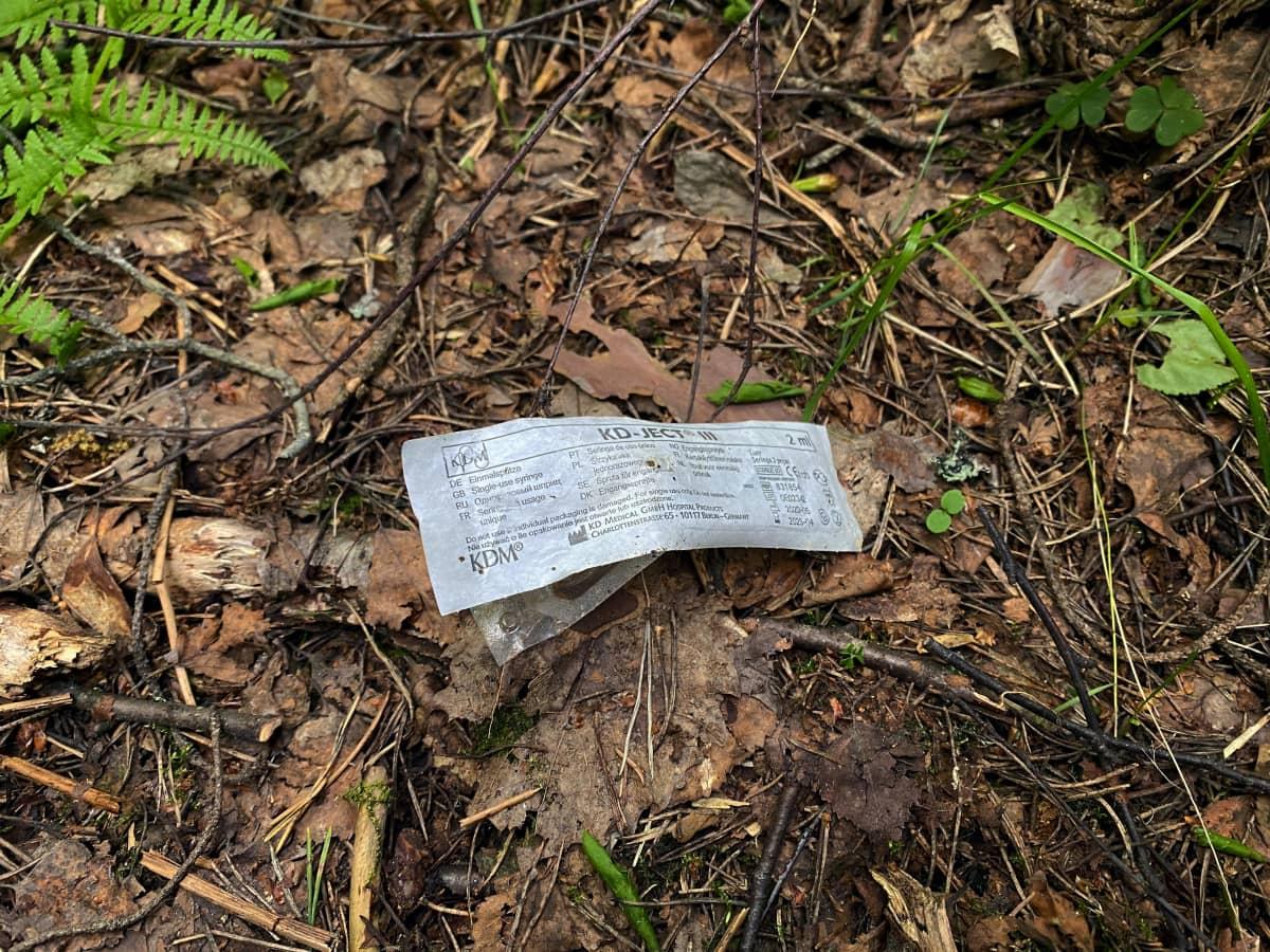 Injektioneulan muovikääre maassa metsässä.