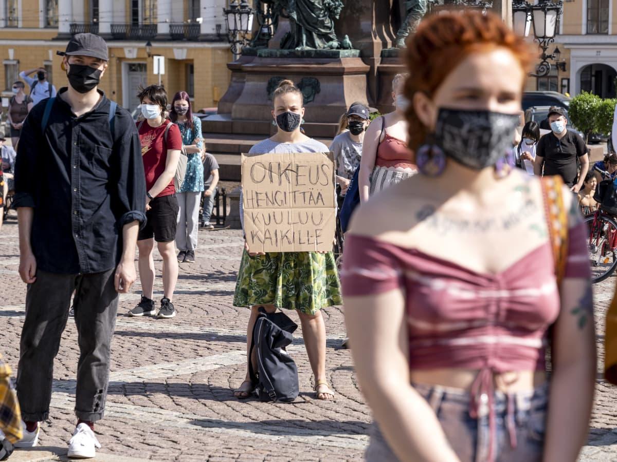 Nainen oikeus hengittää kuuluu kaikille -kyltti kädessä.