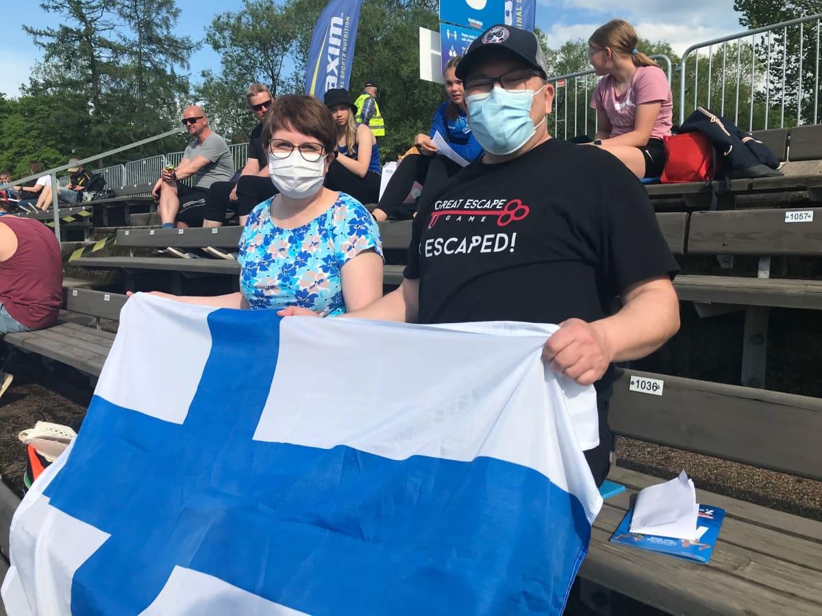 Vesa ja Heli Kuparinen istuvat katsomossa ja pitelevät suomenlippua