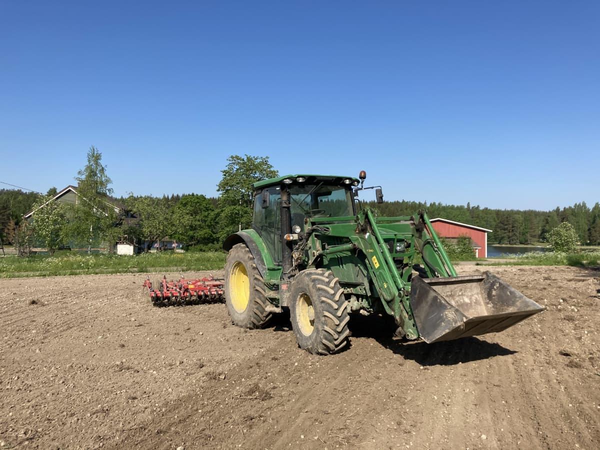 Traktori seisoo vastakynnetyllä pellolla.