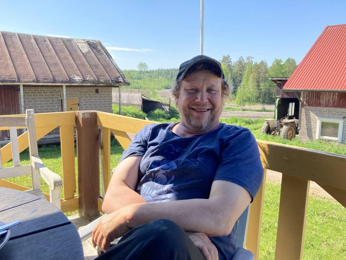 Maanviljelijämies istuu kotitalonsa kuistilla hymyillen.