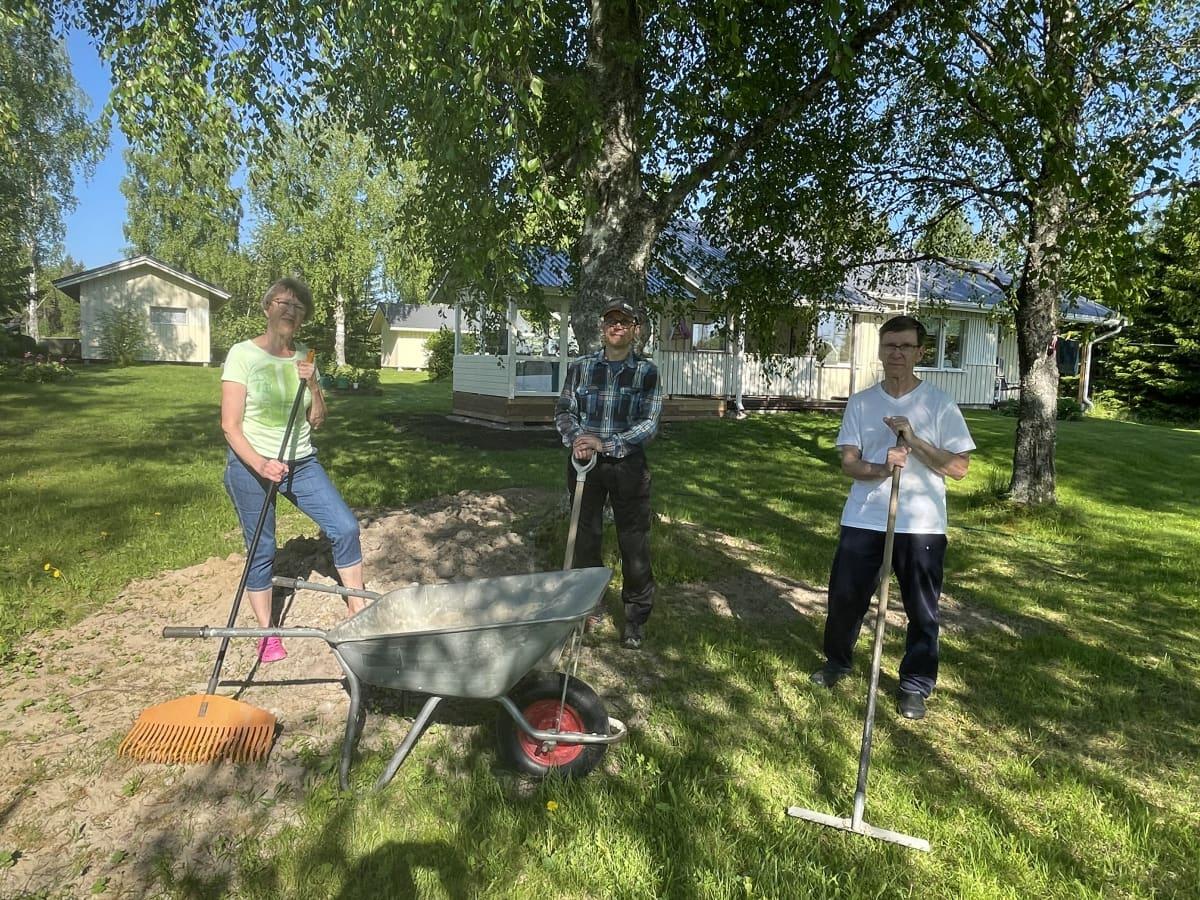Niina, Eero ja Eero karjalainen seisovat kesämökin edustalla pidellen puutarhatyövälineitä käsissään.