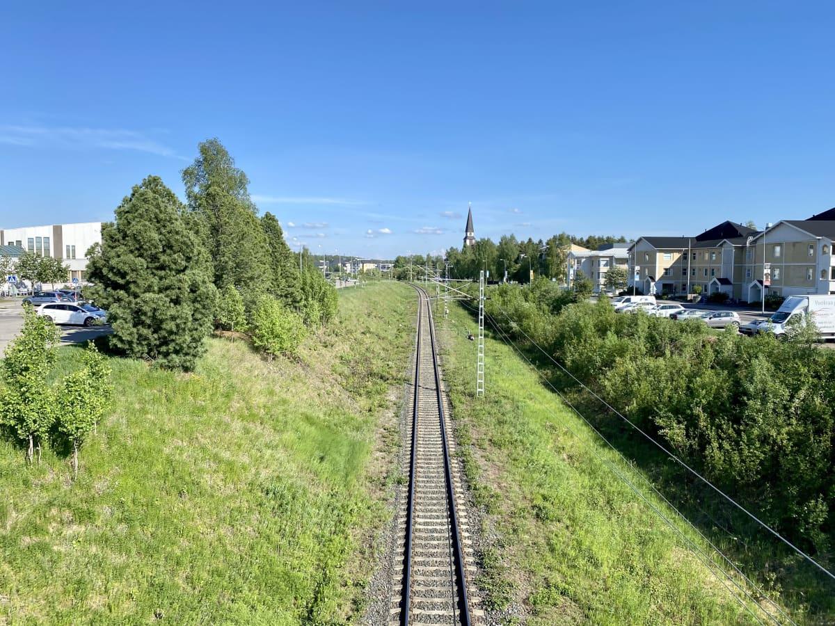 Kuva junaradasta, taustalla näkyy Rovaniemen kirkko