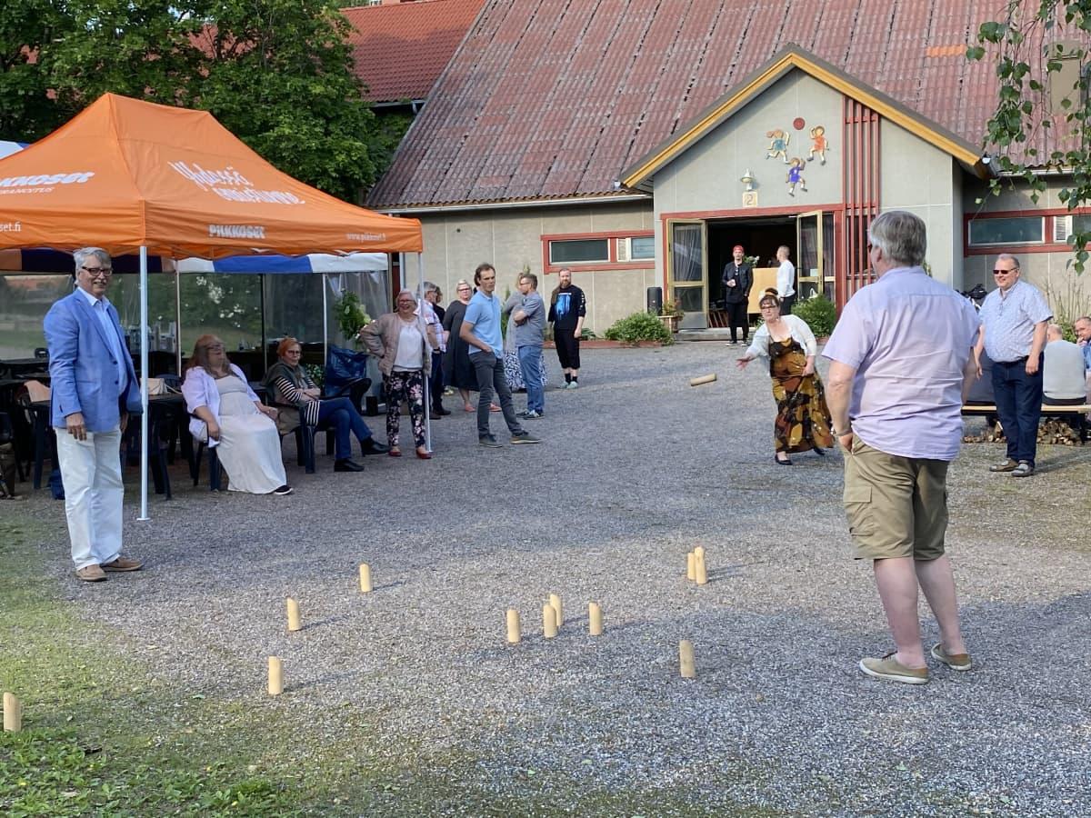 Ihmisiä seuraintalon pihamaalla pelaamassa mölkkyä.