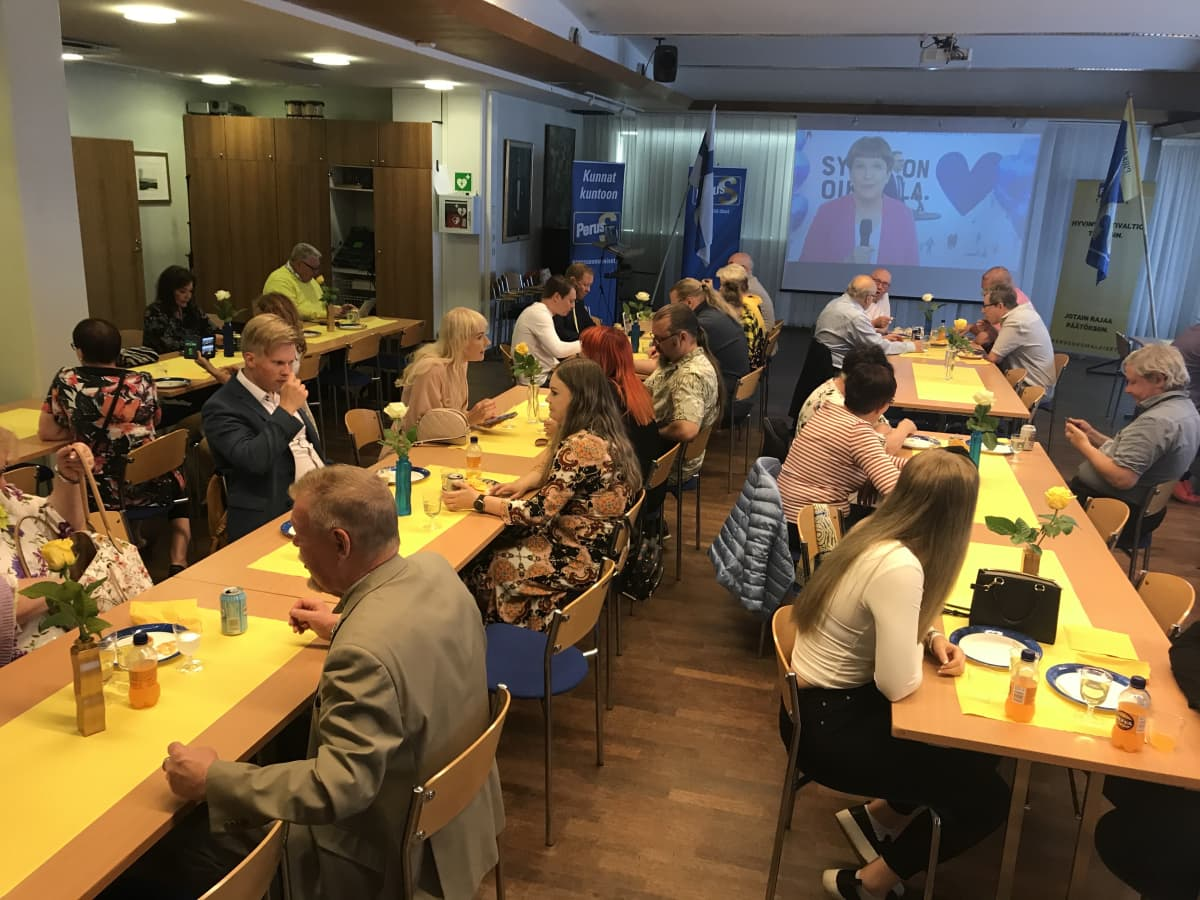 Perussuomalaisten vaalivalvojaiset, missä ihmiset istuvat pitkien pöytien ääressä.