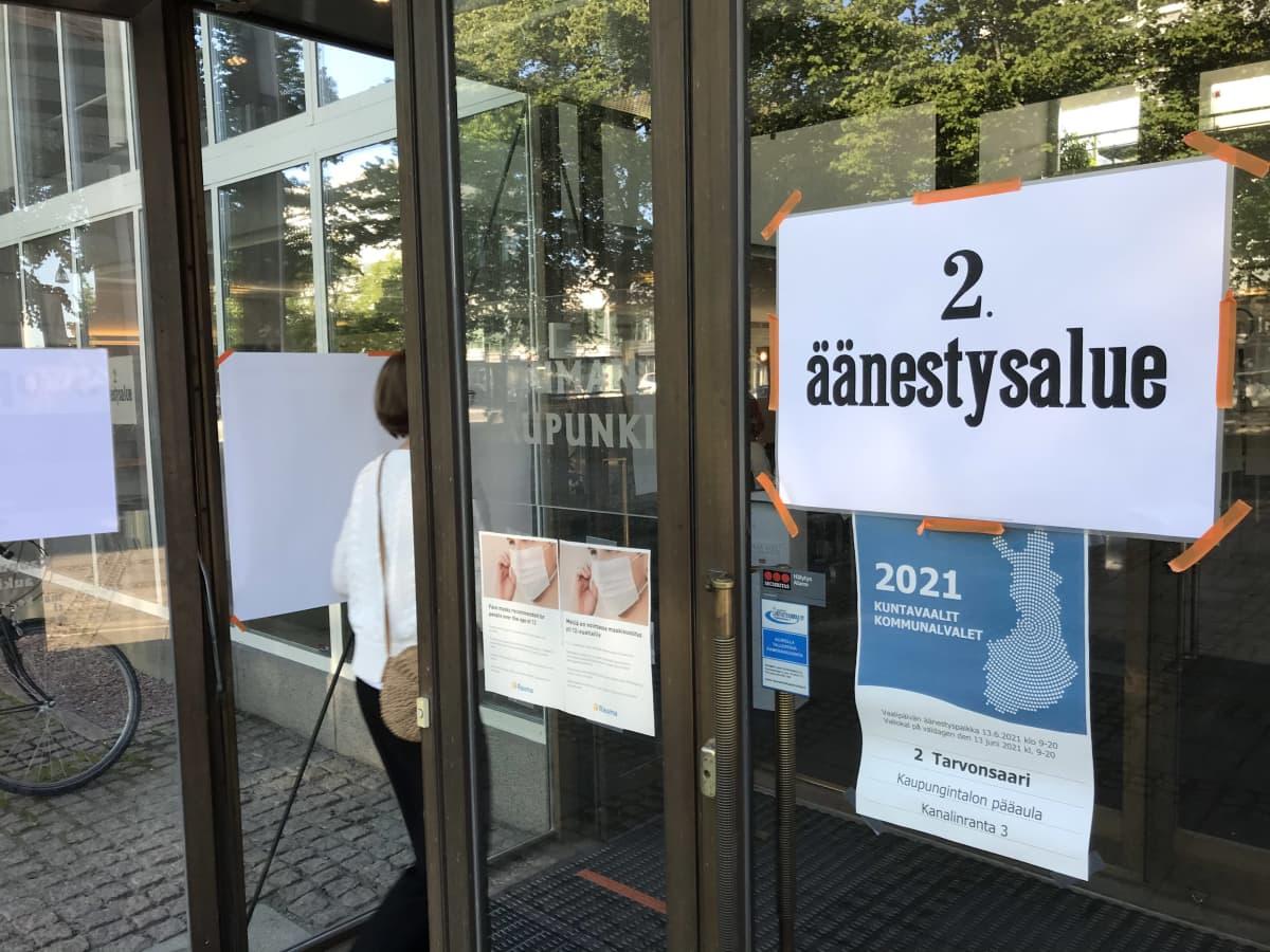 Nainen jonottaa Rauman kaupungintalon ovella kuntavaalien äänestyspäivänä 2021.