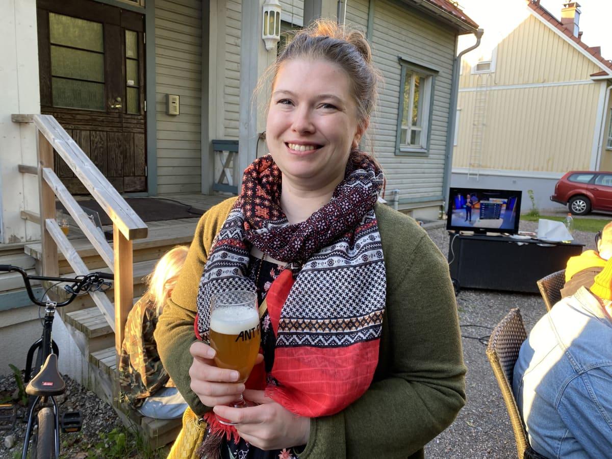 Nutturapäinen nainen hymyilee kameralle oluttuoppi kädessään.