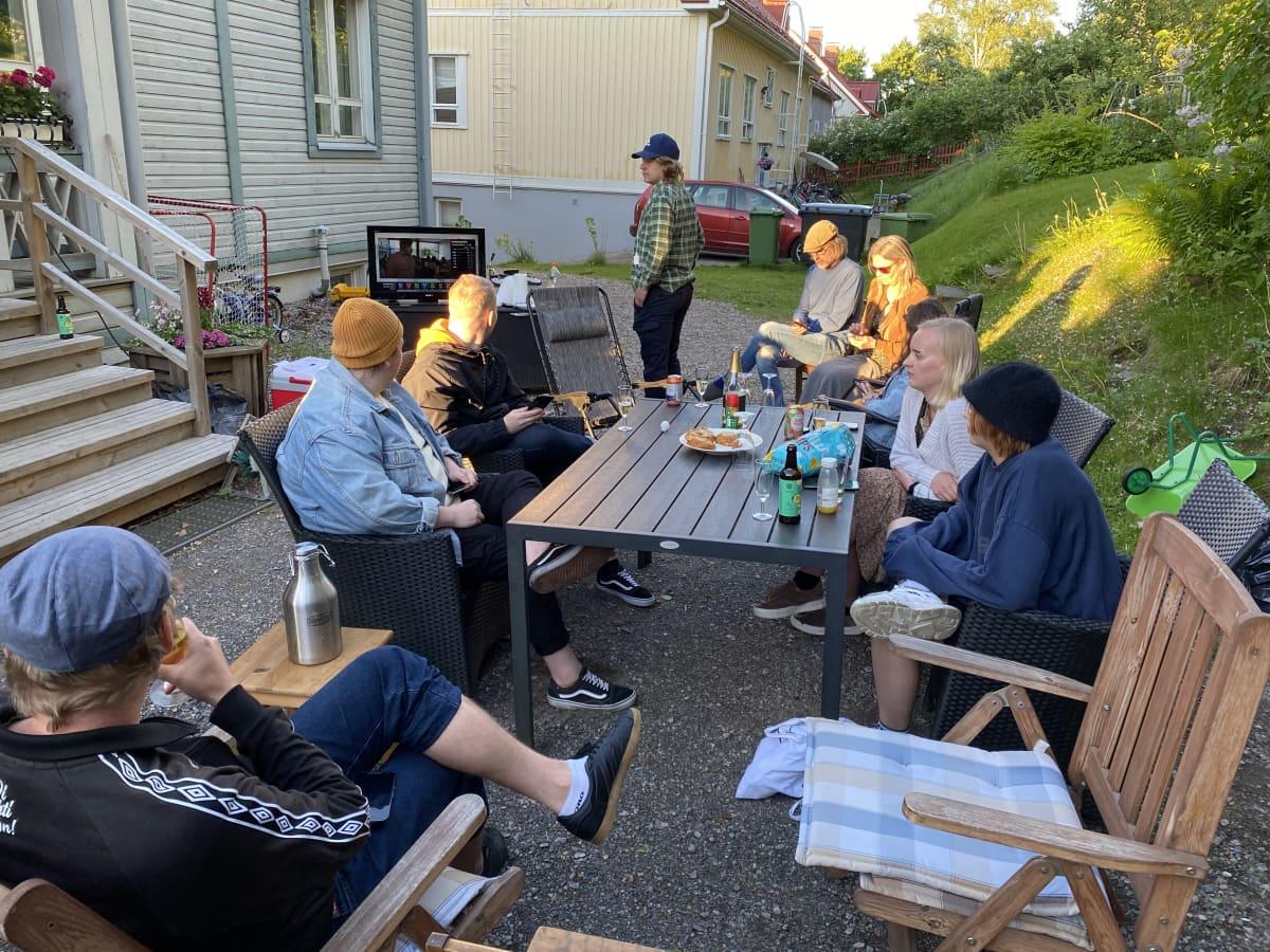 Ihmisiä istuu puutarhapöytien ympärillä vanhan puutalon pihalla.