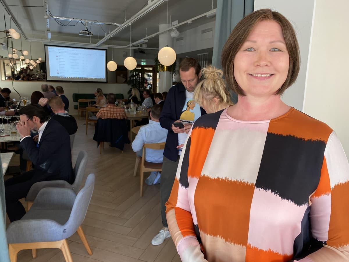 Nainen katsoo kameraan ja hymyilee, taustalla ravintolamiljöö