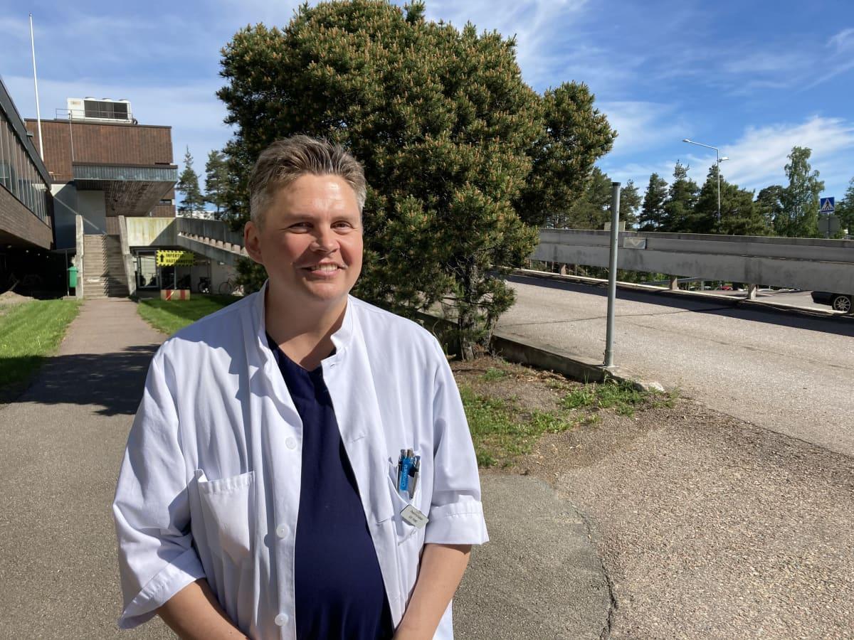 Mieslääkäri seisoo hymyillen auringonpaisteessa, taustallaan Kotkan keskussairaala.