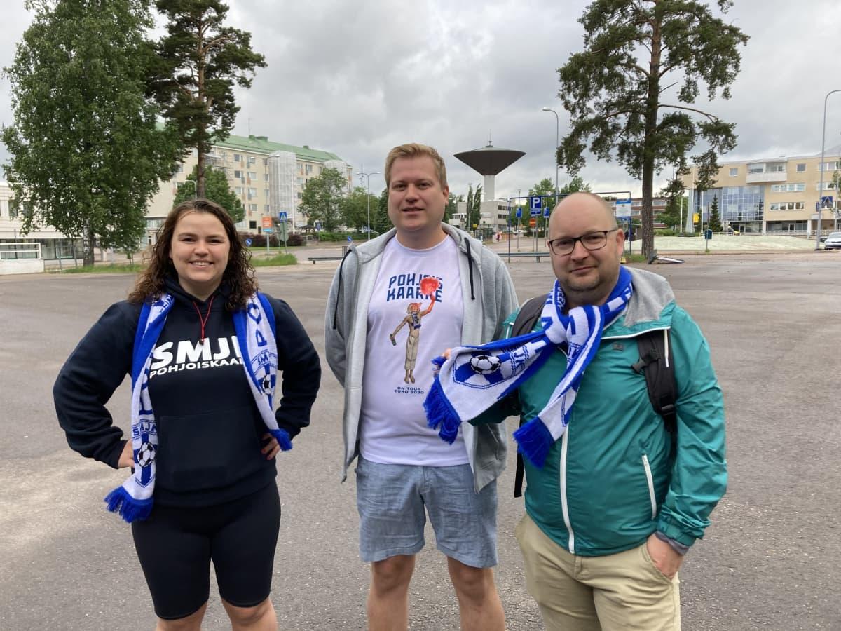 Nainen ja kaksi miestä seisoo Karhulan linja-autoasemalla odottamassa fanien bussikyytiä jalkapallon EM-kisoihin Pietariin.