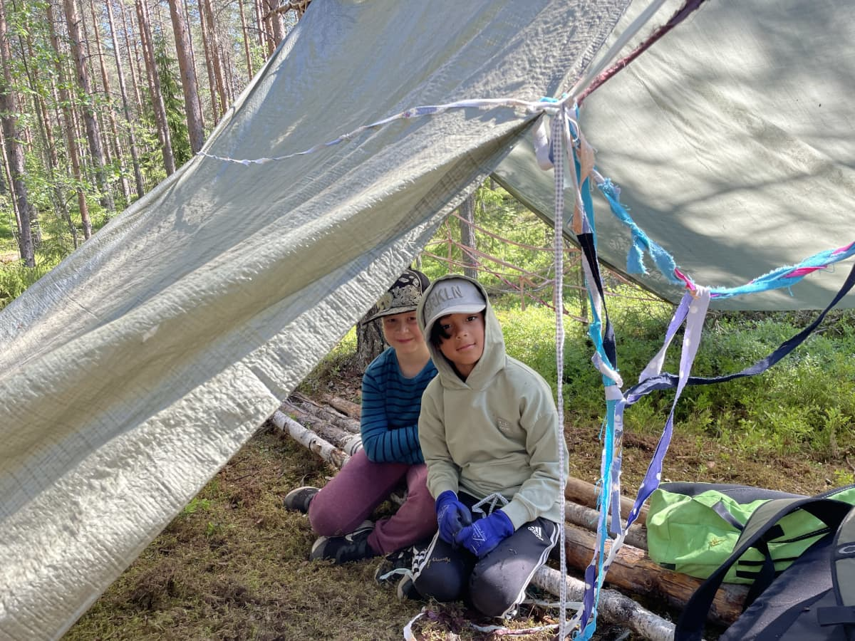Alakouluikäiset Santeri Leinonen ja Matias Palonen istuvat porukalla rakennetun majan sisällä