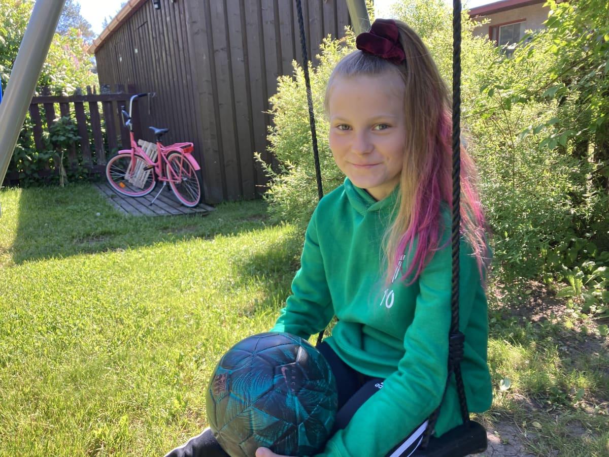 Vihreäpaitainen, hymyilevä tyttö istuu keinussa.
