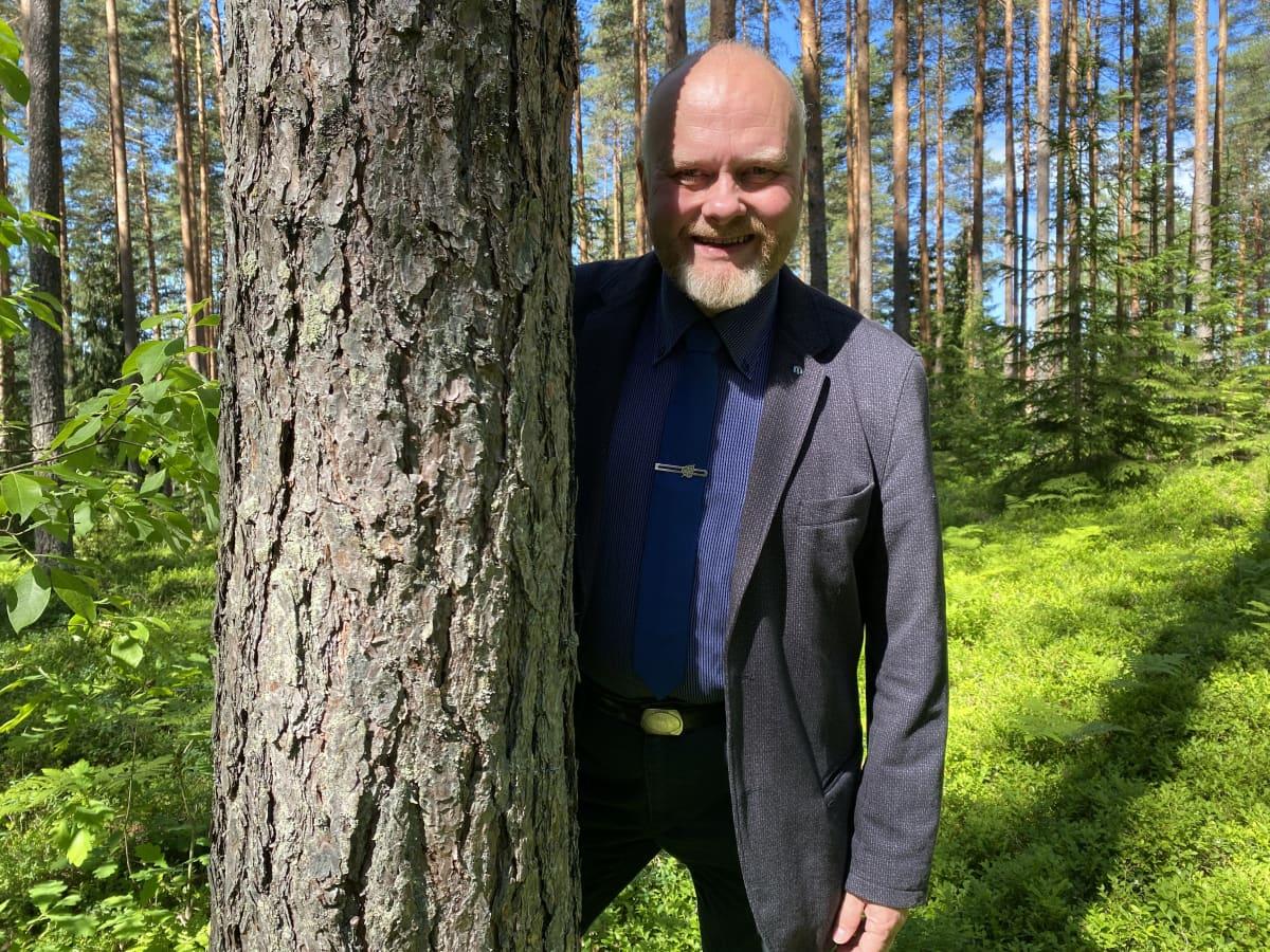 Erä- ja luontokulttuurimuseon projektipäällikkö Timo Kukko seisoo puoliksi havupuun takana puku päällä ja hymyilee.