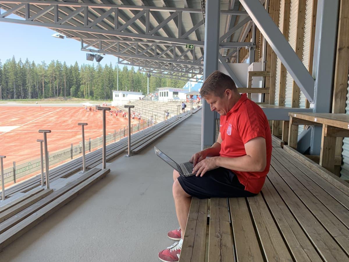 Mies istuu urheilukatsomossa tietokoneen äärellä.