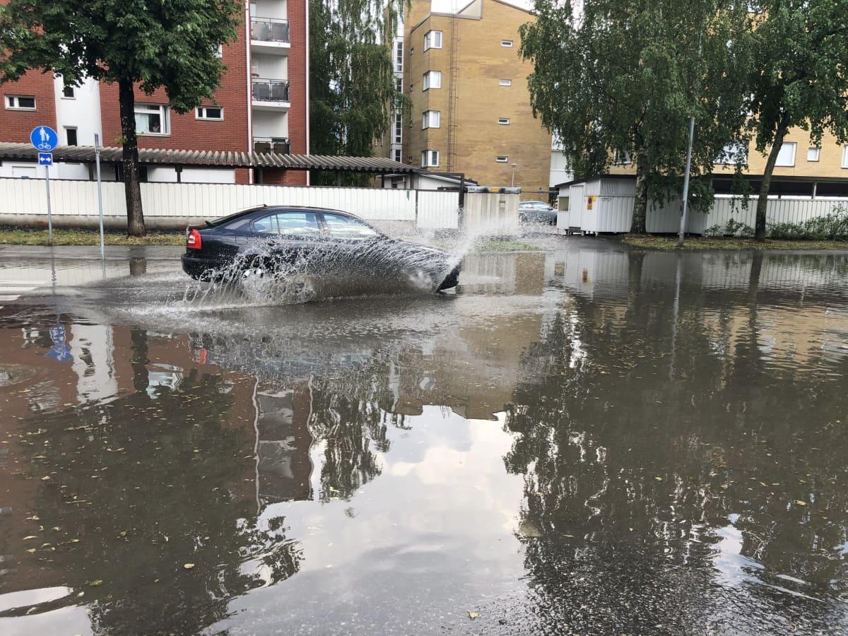 Auto ajaa lainehtivalla Kuopion Satamakadulla rankkasateen jälkeen.