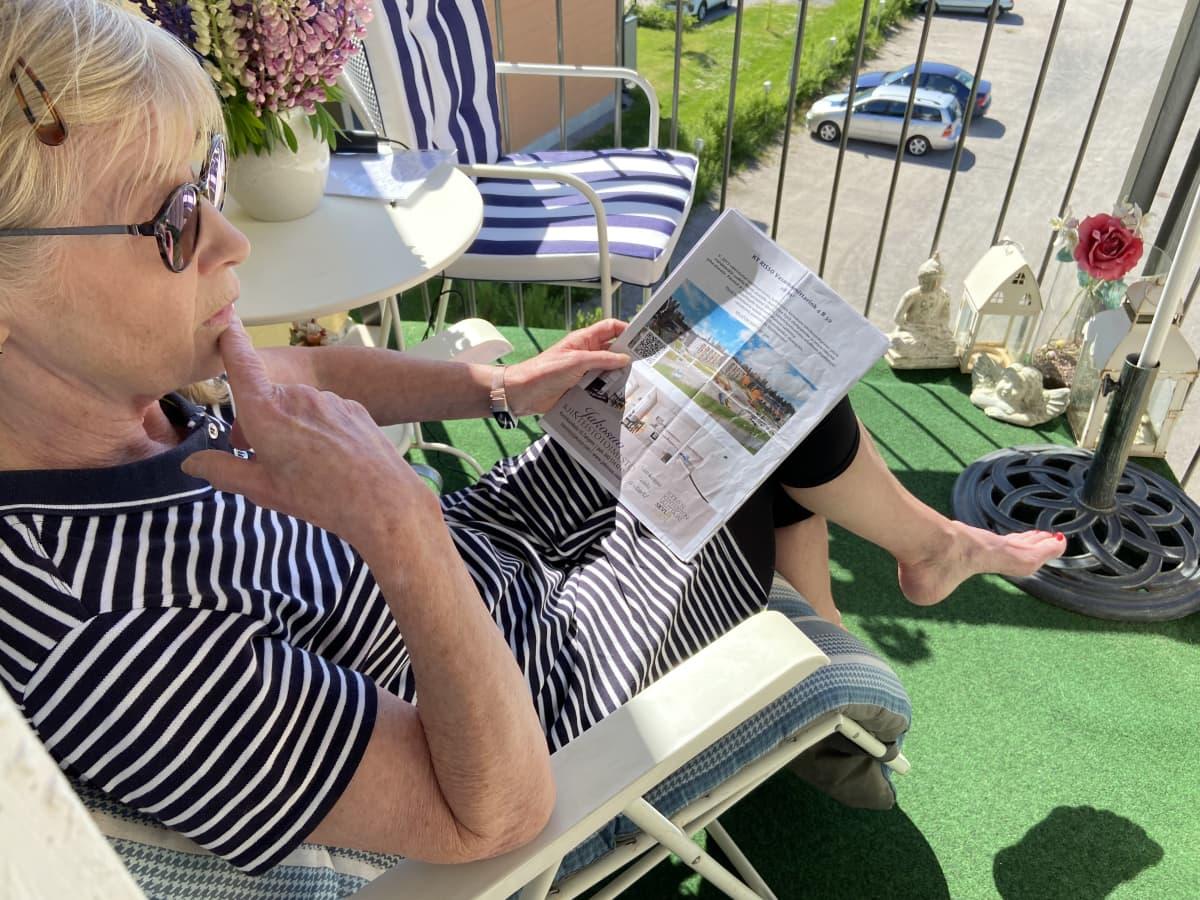 Nainen istuu parvekkeen tuolilla mietteliäänä ja pitää käsissään ostamansa yksiön myyntiesitettä