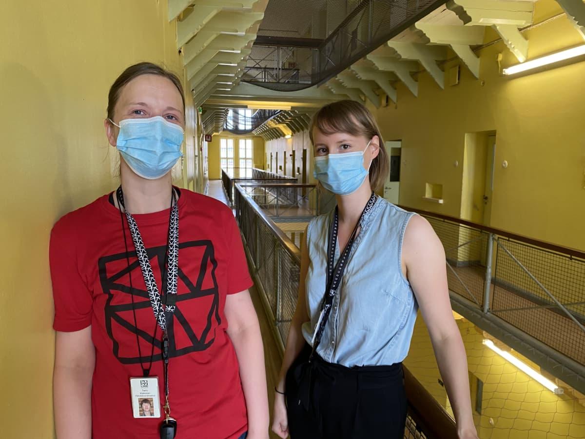 Kaksi naista seisoo vankilamuseon käytävällä maskit kasvoilla, taustalla näkyy vanhan vankilan portaikko
