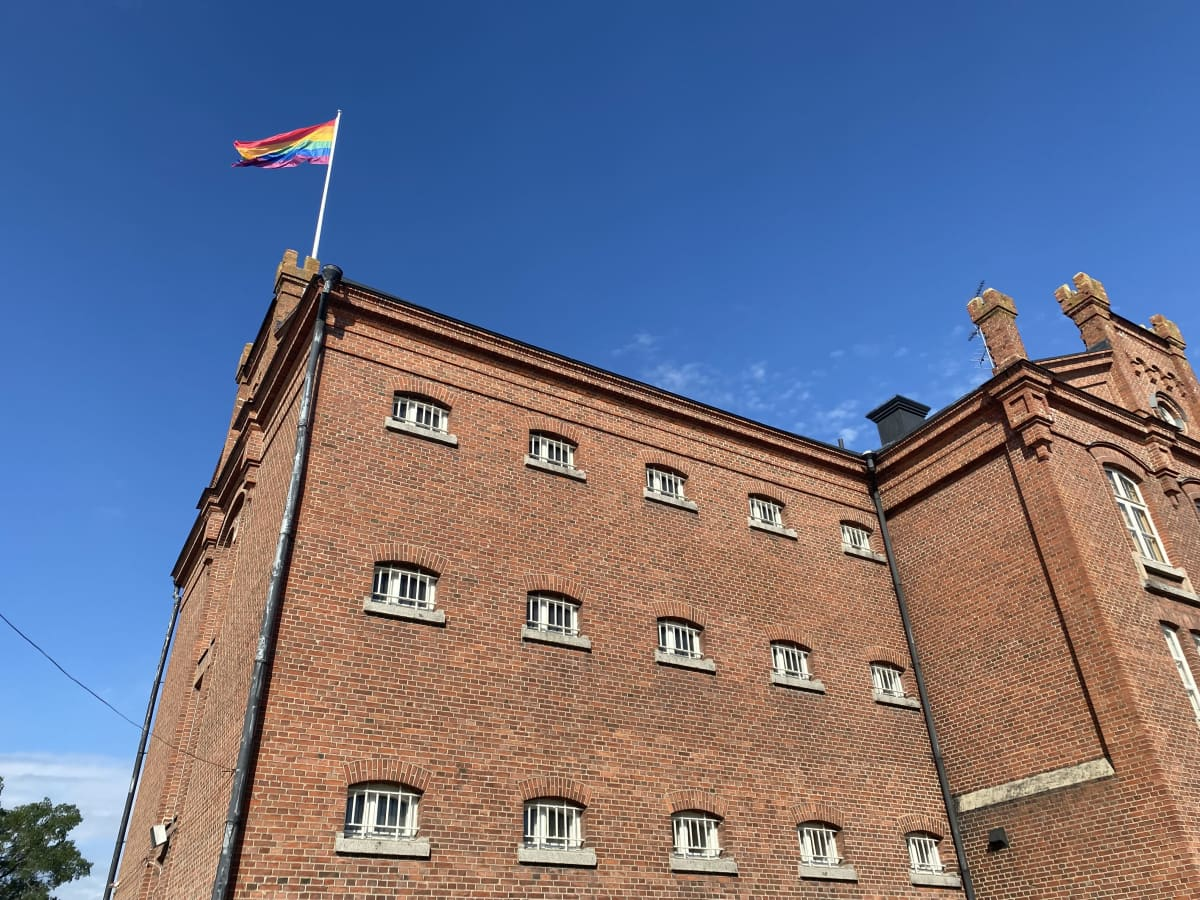 Tiilisen vankilamuseon päädyssä katonharjalla lippusalossa liehuu pride-lippu