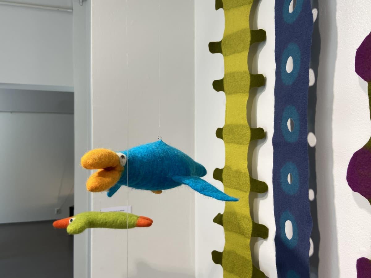 Taidennäyttelyssä roikuu siimoissa huovasta tehtyjä värikkäitä lintuja