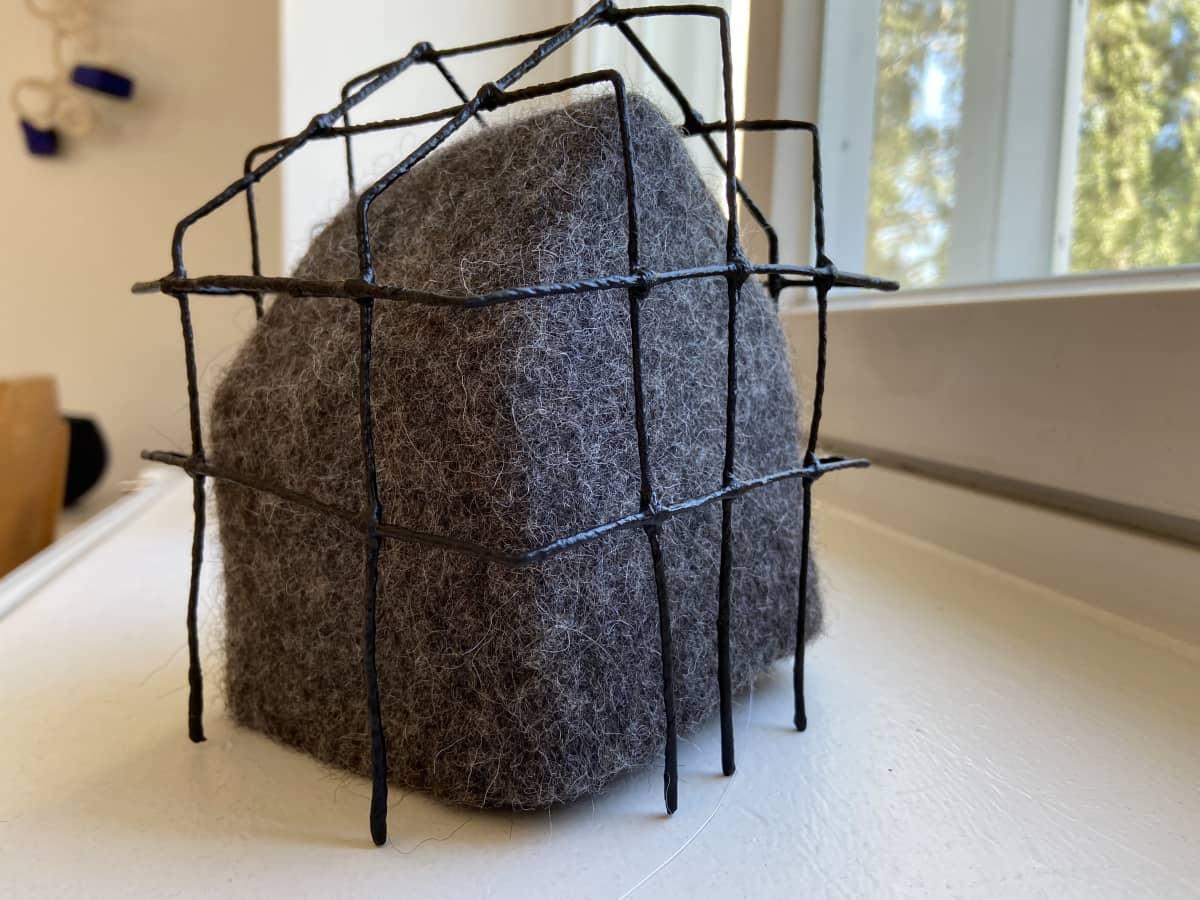 Huopataidenäyttelyn ikkunalaudalla huovutettu teos nimeltään Isolation