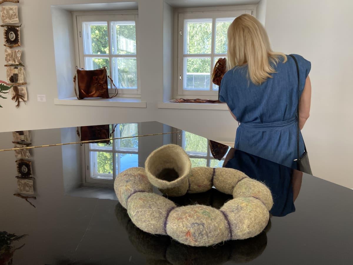 """Nainen katsoo Jämsän huopataidenäyttelyn teoksia , flyygelin päällä on teos nimeltään """"Tunnelin pää""""ia"""
