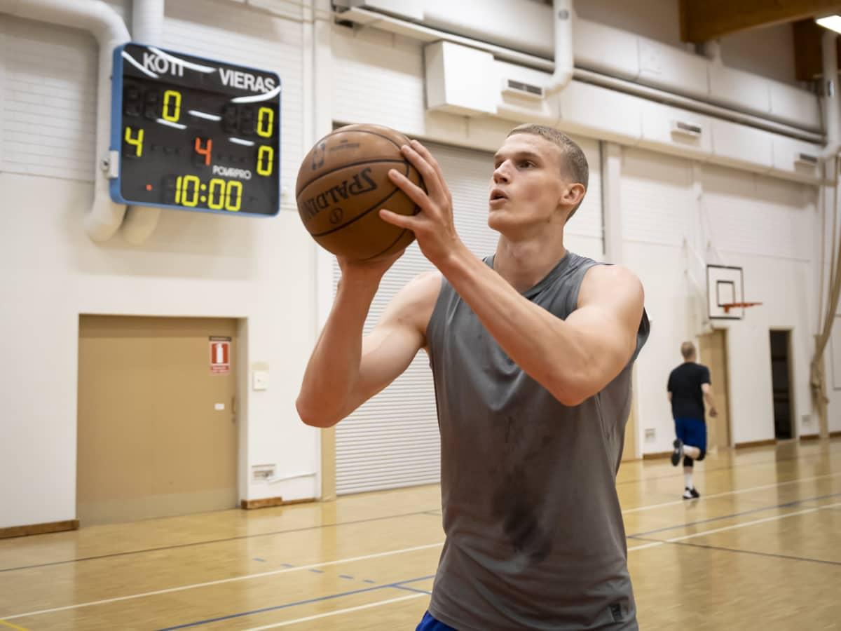 Lauri Markkanen heittää koripalloa koulun liikuntasalissa.