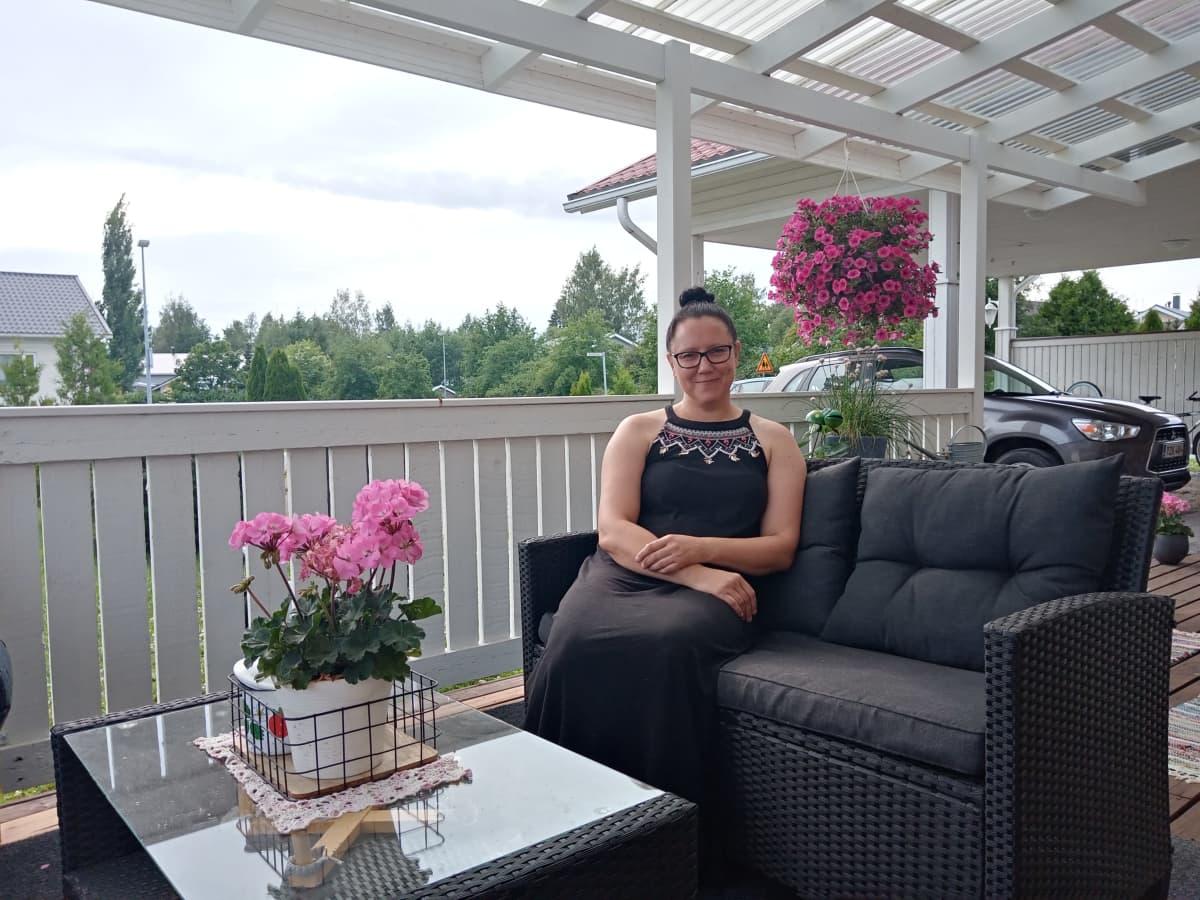 Katariina Leskelä istuu terassin sohvalla.