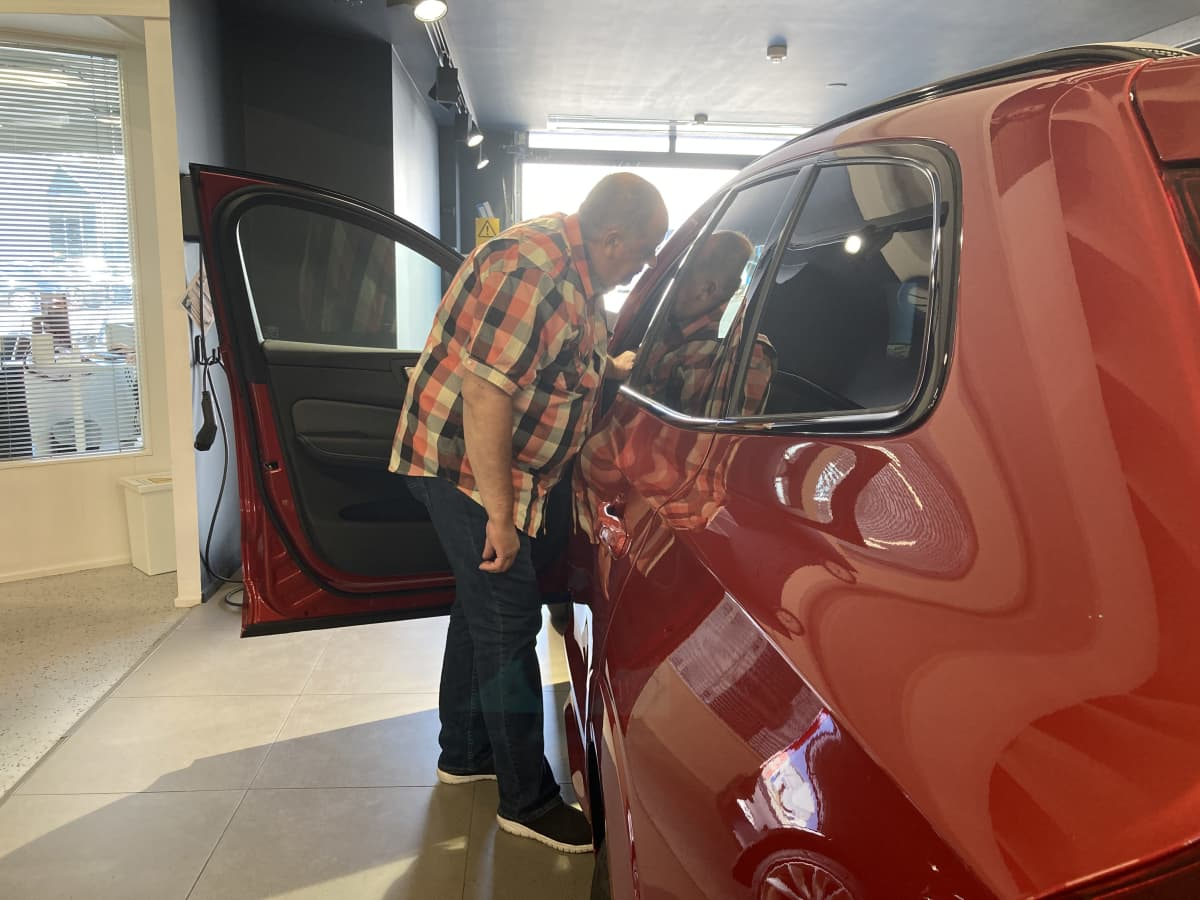 Alahärmäläinen Pentti Korpi tutkailee uutta hybridiautoaan.