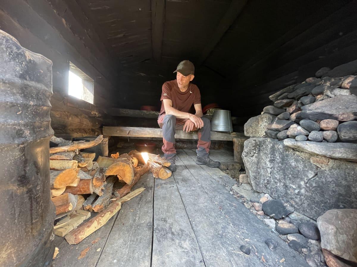 Kolttien luottamusmies Veikko Feodoroff katsomassa Suomujoen kolttakentän savusaunaa.