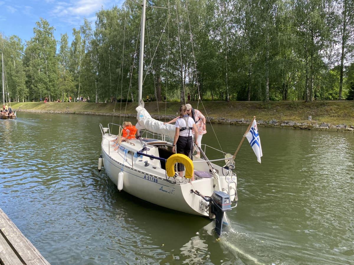 Valkea purjevene lipuu kanavassa