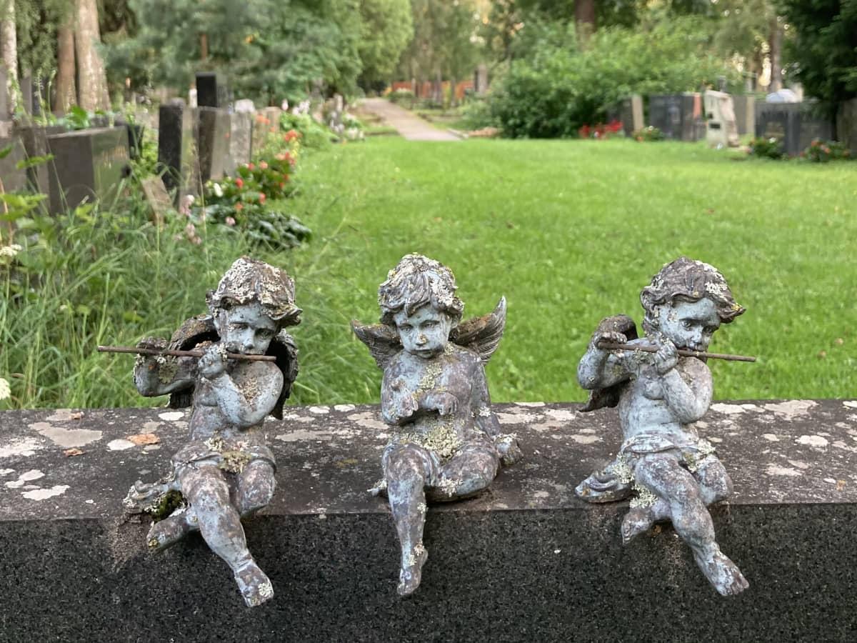 Kolme enkelifiguuria istuu hautakivellä