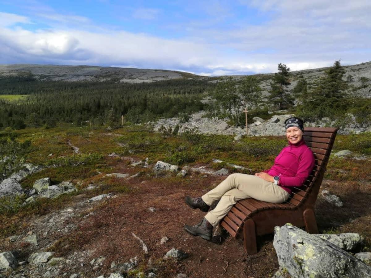 Nainen istuu penkillä tunturimaisemassa.