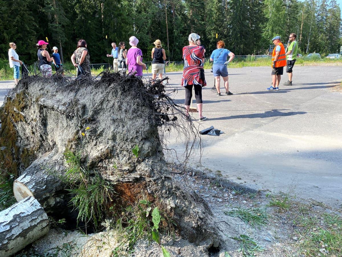 Ihmisiä kokoontuneena siivoustalkoisiin tyhjälle tontille, etualalla kaatuneen puun juurakko.