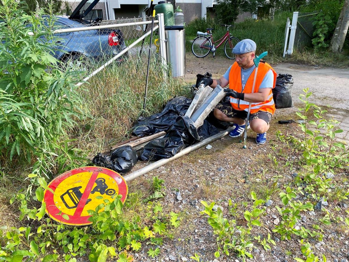 Efe Altingediz tutkii siivoustalkoissa löytynyttä muoviputkea. Maassa on myös useita mustia jätesäkejä ja liikennemerkki.
