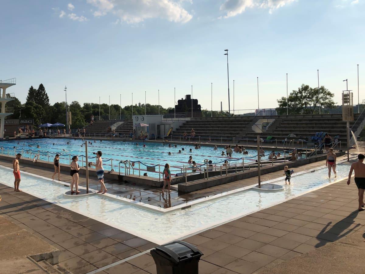 Uimareita ja vesijuoksijoita Samppalinnan maauimalassa heinäkuussa 2021..