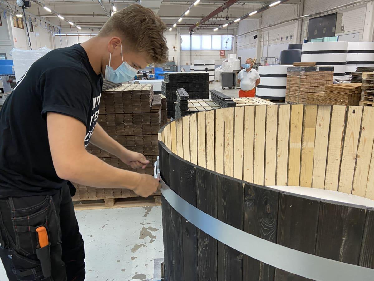 Nuori mies asentaa paljujen tuotantolaitoksella paljun vannetta Kirami Oy:n tuotantolaitokselal Sastamalassa