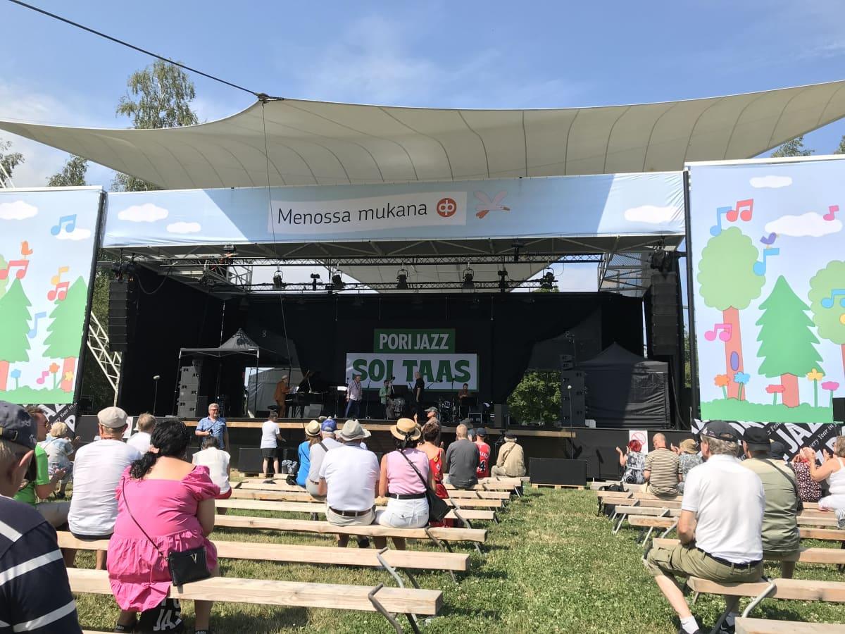 Yleisöä istuu puupenkeillä esiintymislavan edessä, jossa esiintyy Eino Grön