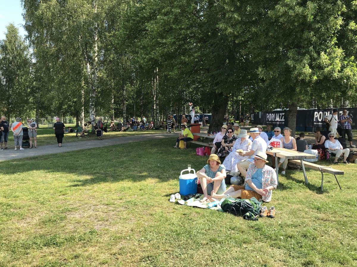 ihmisiä istuu koivun varjossa nurmikolla. Taustalla suurella Pori Jazz-tekstillä varustetut mustapohjaiset mainoslakanat
