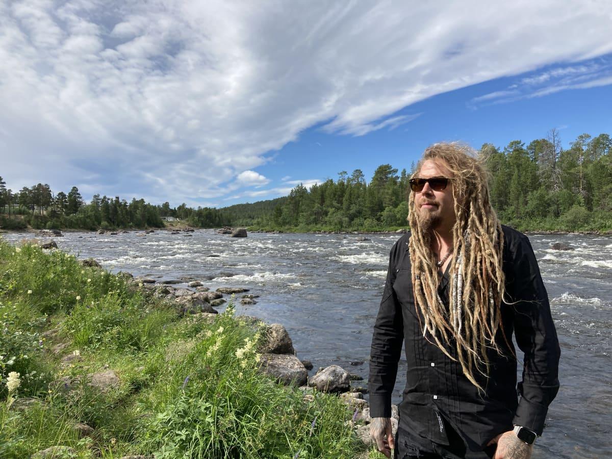 Muusikko Jonne Järvelä seisoo Juutuanjoen rannalla.