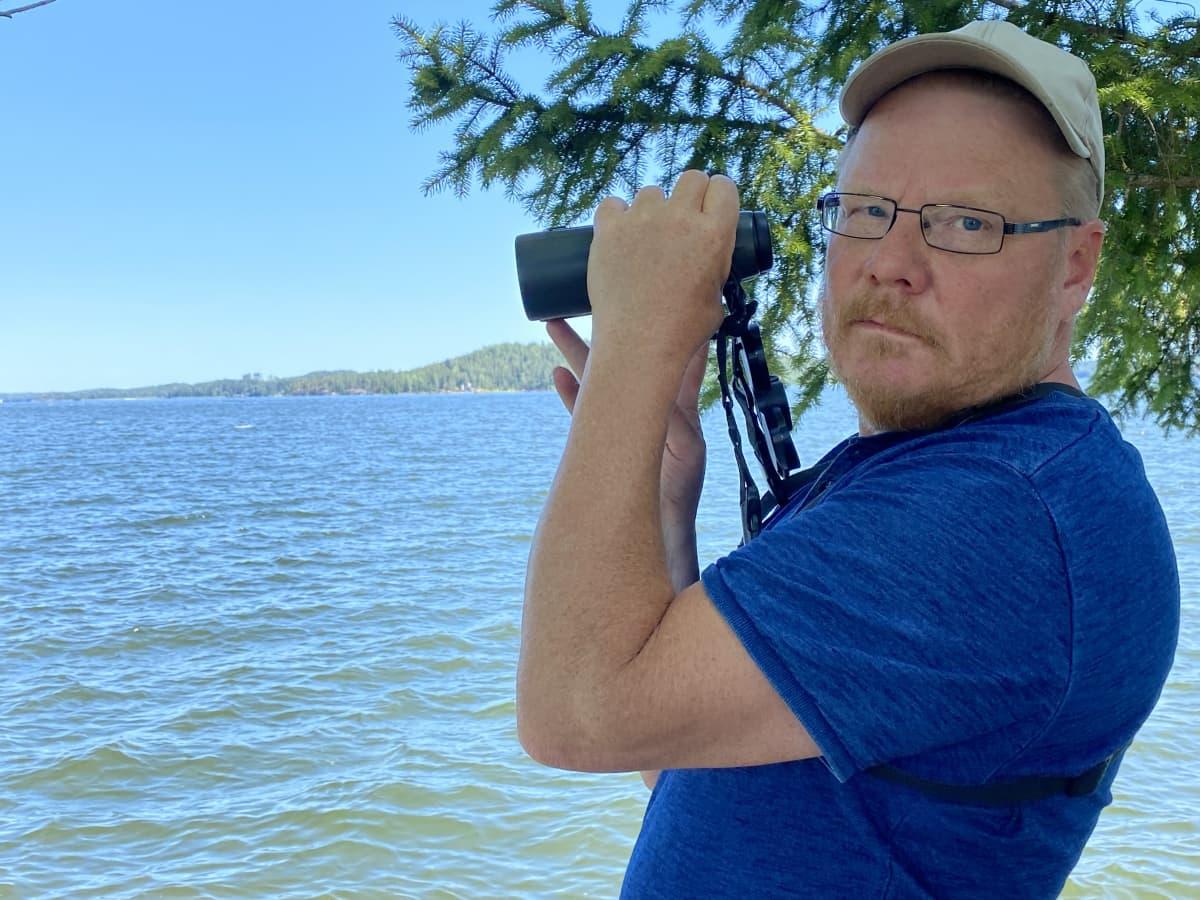 Siniseen t-paitaan pukeutunut lippispäinen mies, katsoo kameraan. On kohottanut kiikarin kohti taustalla olevaa järveä