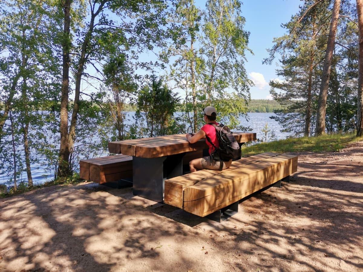 Taukopaikka, jossa puisen pöydän ääressä istuu selkä kameraan päin ulkoilija puisella penkillä. Taustalla vesistö.