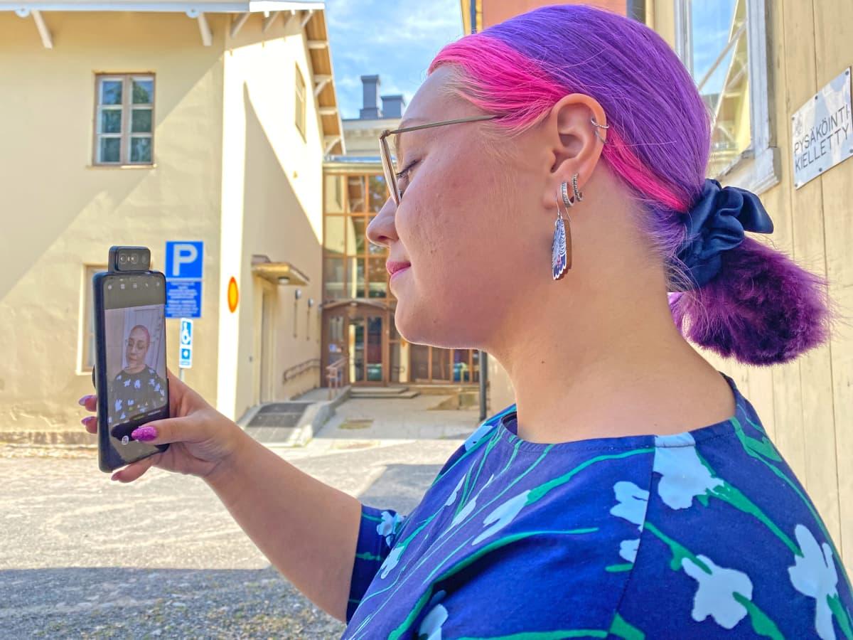 Nainen ottaa itsestään selfietä puhelimella