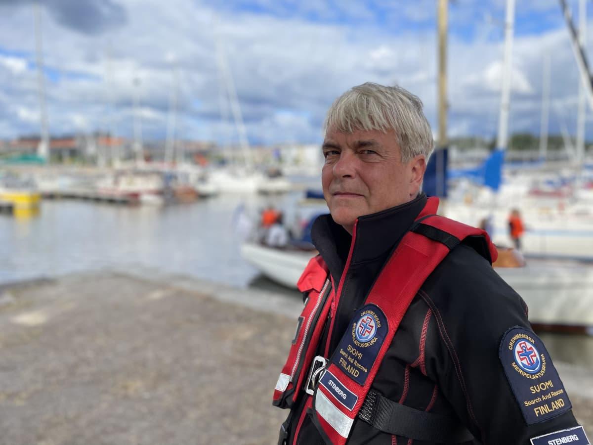 Marko Stenberg seisoo satamassa, taustalla purjeveneitä.