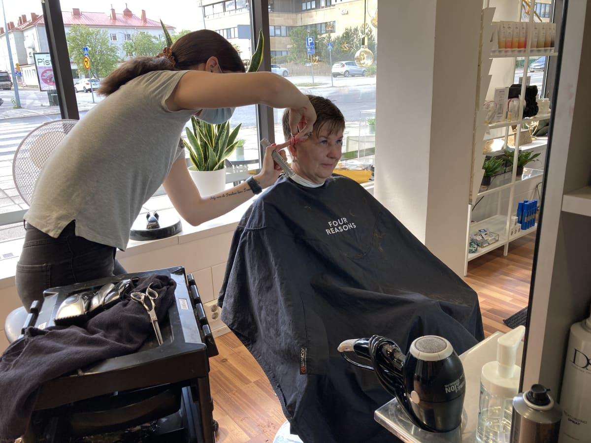 Parturi-kampaaja Eveliina Kalliomäki leikkaa Anna-Maria Kosken hiuksia.
