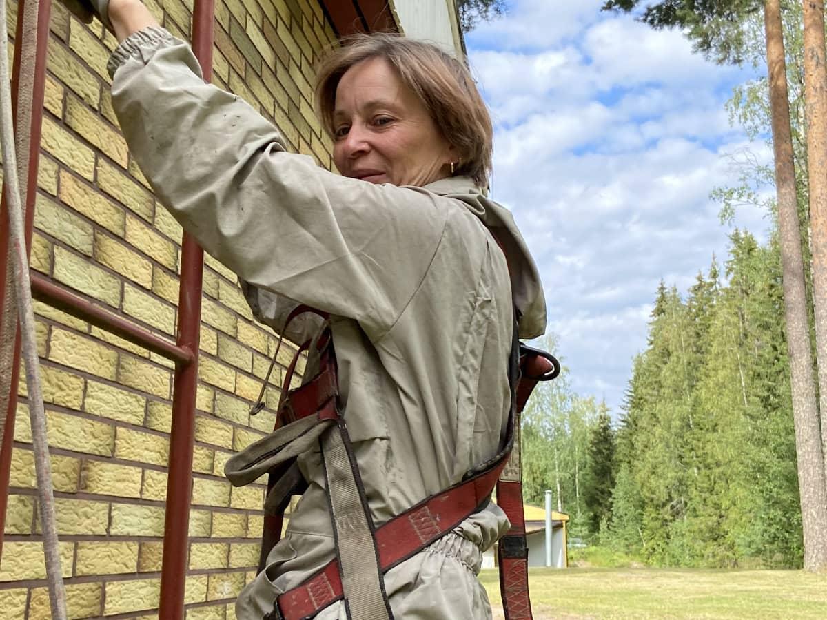 Maalari Mervi Salminen, Temagroup Oy:n toimitusjohtaja, on nousemassa suojavatusteineen talon katolle tikapuita pitkin